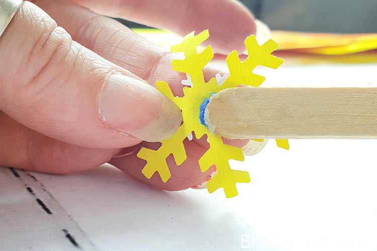 Using The Lolly STick To Place Glue Onto The Paper Snowflake